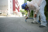 Workers from Custom Environmental clean up possible traces of asbestos outside an apartment...