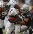 (OAKLAND, CA., OCTOBER 17, 2004)  Denver Broncos' #34, Reuben Droughns, left, pulls Oakland...
