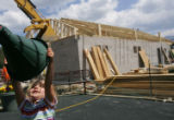 Abby Olsen (cq), 3, of Denver, plays on playground equipment next to a construction project in...