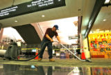 Mike Avalos vacums an area where old carpet was removed, in the main terminal at DIA, Tuesday...
