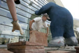 Calvin Crouse, 18, and Andrew Stenger, 21, of Autumn Gold Landscapes lay flagstone under the bear...