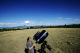 Daniel Champion, of Tuscon, Ariz. dismantles his telescope before leaving on the final day of...