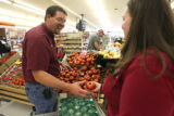 Zach Deal (cq) and his wife Angie Deal (cq) stock tomatoes at Edwards market in Fort Morgan on...