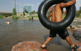 Dominic Lucero, of Denver, hops from rock to rock while tubing at Confluence Park in Denver,...