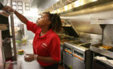 Monique Davis (cq), works on putting together a sandwich, Thursday afternoon, July 10, 2008,...