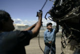 Mario Cabrera (cq), left, and Raphael Moreno (cq), both from Denver, try to take a transmission...