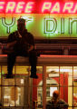 A girl is trapped in Mickey's Diner ias a riot policeman sits on top of the diner downtown St....