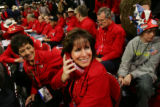 Colorado delegates Shari Williams, center, talks on a phone while Lilly Nunez, left, listens in on...