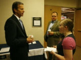 U.S. Sen. John Thune, R-S.D., left, talks to Colorado delegate Kimberly Peticolas as aide to...