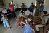The Johnson family kids--all eight of them--rehearse in their living room for an upcoming...