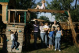 (from left) 4 year-old Hyrum Anderson (cq) hangs on to a rope as the rest of his family pose for a...