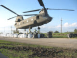 Sandbags weighing 4,000 pounds each are hooked to an Army National Guard CH-47 Chinook helicopter...