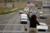 DM0929  Terri McNabb, 48, of Thornton waves a flag on the 88th Avenue bridge over Interstate 25 to...