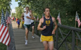Runners cross a bridge that leads them to the finish line during the Division 2-B boys race at the...