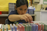 Jamilyn Castillo uses tubes, filled with colored beads, to work on a math problem, in her 2nd and...