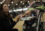 Tracie Sudermann, from Lakewood, feeds her 5-month-old son Joseph Sudermann before Gov. Sarah...