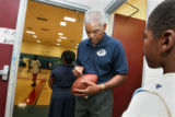 Former Broncos quarterback Marlin Briscoe signs a football for a child at the Eastman-Fairfield...