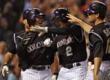 Colorado Rockies rookie shortstop Troy Tulowitzki is met at home plate by teammates Chris...