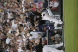 Colorado Rockies third base coach Mike Gallego congratulates catcher Yorvit Torrealba after he...