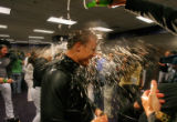 Colorado Rockies pinch hitter Jeff Baker gets drenched with champagne in the locker room after...