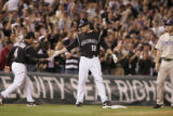 Colorado Rockies coach Mike Gallego congratulates Seth Smith at third base after his triple in the...