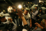 The Colorado Rockies' Matt Holliday receives a champagne shower in the locker room after defeating...