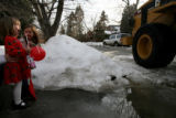 Kiley Petracek, 3, and friend Neave Fleming, 5, react to a passing tractor as it removes ice and...