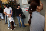 Harles Cone strokes the face of his daughter, Lexie Cone, 6, as he and other voters wait in line...