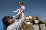 Chuck Gully holds up his youngest daughter, Erika Gully, 11 months, outside their home on the...