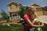 MJM582  Maggie Barnhill (cq), embraces her daughter, Ceci Barnhill, 9, outside their family's...