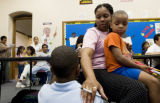 (DENVER, Colo., Aug. 26, 2004)  Francine Jackson holds her son, James, 4, while comforting another...