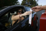 Early voting began today in Colorado and already hundreds of votes have been cast. A woman drops...