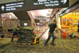 Mike Hart, left, and Rahn Richards cart away some old carpet in the main terminal at Denver...