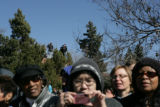 People stand on the corner of Montview and Colorado as President Obama's motorcade drives by at...