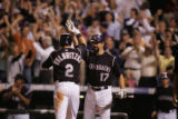 Troy Tulowitzki is congratulated by Todd Helton as he scored on a single by Matt Holliday in the...