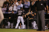 Rockies pitcher La Troy Hawkins gets high fives from the Rockies dugout after retiring the Padres...
