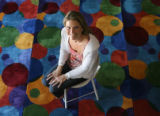 Sheri Schmelzer seated on a carpet at her company's Boulder, Colorado headquarters. Schmelzer's...