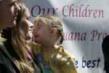 Laura Evans (cq) holds her daughter Linet Evans, 3 (her mom) in front of a sign for legalizing...