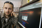 Danny Ledonne sits next to a screen of the game he created in  Milagros Coffehouse in Alamosa. He...