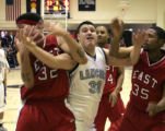 Lincoln's #33, center,  fights for the ball in the 3rd period against east's #32 Mookie Gilbert...