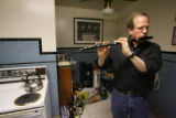 Rod Garnett retreats to the kitchen to hear his flute better during rehearsal with bandmates in...