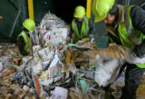 Workers (who wished to not give their names) dismember a block of paper debris before they are...