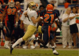 (DENVER, CO., DECEMBER 29, 2004)  University of Colorado's punter, #29, John Torp, left, races for...
