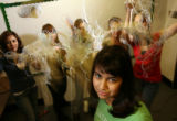 MJM340  As knitting yarn flies through the air, Karla Garcia (cq), 16, center, poses for a...