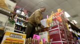 Dawit Beyene (cq), owner of E & S Liquors, 6460 E. Yale Ave, in his store restocking, Friday...