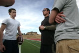 Nate Sassman instructs quarterbacks Brice Queener, left, Cory Garrelts , right,  after school at...