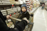 1 year-old Miles Schiskowsky (cq) rides a shopping cart along with his mother, Kaycee Schiskowsky...