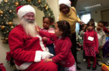(Denver, Colo., December 16, 2004) Carla Gonzalez, 3, touches the beard of Santa Claus, Pat kelly,...