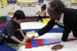 "Kindergarten teacher Linda Alston helps Damien Martinez, 6, do his ""work"" in her..."