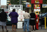 Downtown commuters pay an electronic machine to park at 13th Ave. and Bannock Street Tuesday ...